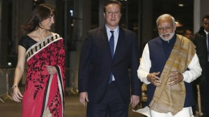 India's prime minister Narendra Modi walks with Prime Minister David Cameron and his wife Samantha in a backstage area at Wembley Stadium