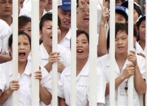 Workers react as they stand by a fence during a strike at a Honda Motor vehicle manufacturing plant in Zhongshan, Guangdong province June 10,2010. REUTERS/Tyrone Siu